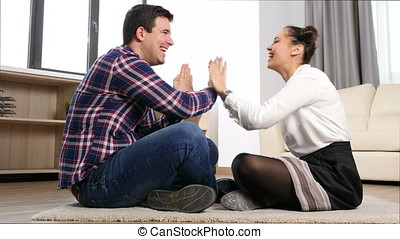 Coupleon the floor of their living room playing toghether
