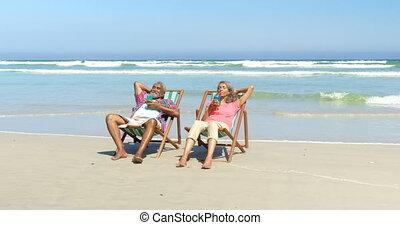 couples aînés, actif, africaine, avoir, vue, boissons, transat, américain, plage, 4k