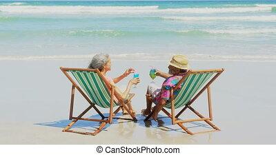 couples aînés, actif, africaine, grillage, vue, arrière, boissons, transat, américain, 4k, plage