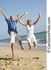 couples aînés, apprécier, vacances plage, sauter dans, air