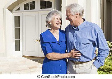 couples aînés, debout, dehors, maison
