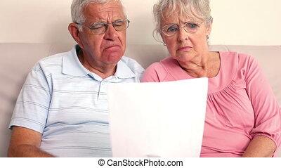couples aînés, inquiété, lecture, doc.