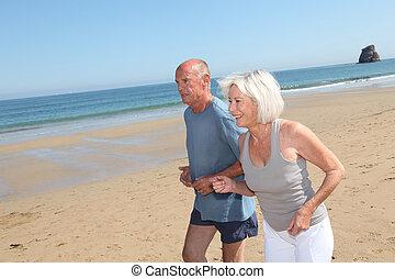 couples aînés, plage, jogging, sablonneux