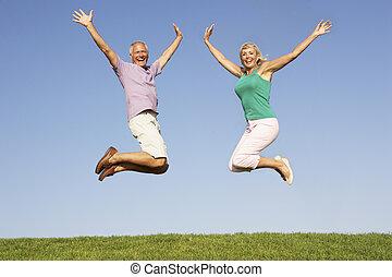 couples aînés, sauter dans, air