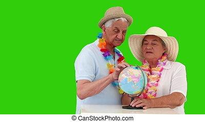couples aînés, vacacion, globe mondial, regarder