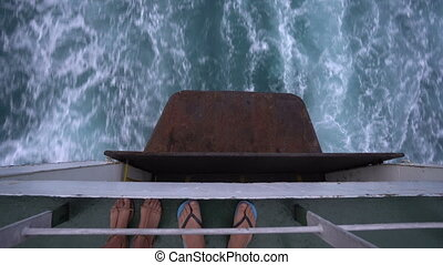 Couple's feet on the boat and sea wave behind large cruise ship