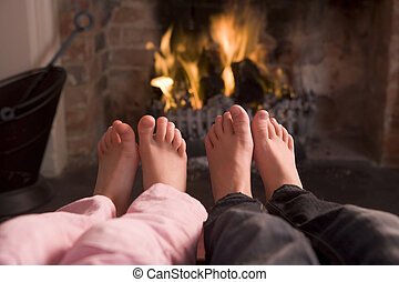 Couple\\\'s feet warming at a fireplace