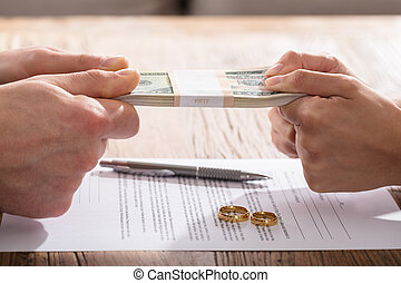 Couple's Hand Holding Currency Over The Divorce Agreement