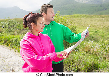Couples holding a map and looking ahead