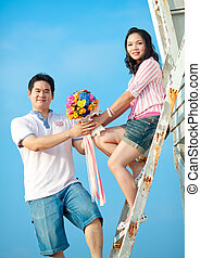 couples holding beautiful flowers bouquet together on the beach