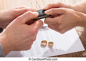 Couple's Holding Car Key Over The Divorce Agreement