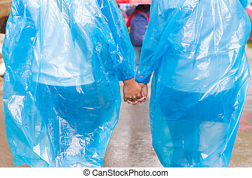 Couples in raincoat holding hands walking on rain