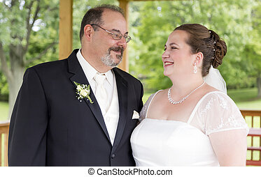 New husband and wife share a loving gaze on their wedding day.