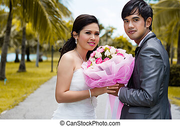 Couples of groom and bride holding bouquet flowers in her hand