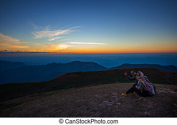 couples of man and woman sitting on top of mountain scene with beautiful sunset sky on high mountain