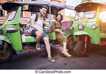 couples of young traveling people sitting on tuk tuk bangkok...