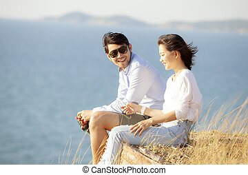couples of younger asian man and woman relaxing with happiness on vacation beach