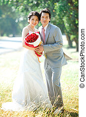 couples portrait of bride and groom on beautiful meadows with rose bouquet
