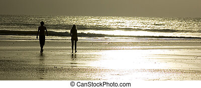A couple walking through the beach during sunset