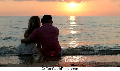 Couples Sit On The Beach