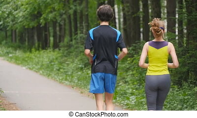 Couples take vacations jogging in the forest, slowmotion -...