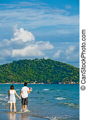 couples walking by hand in hand along the beach with gentle ripple
