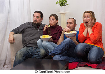 Couples watching a horror movie - Two couples sitting...