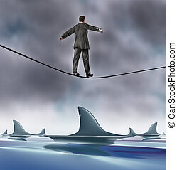 Courage and risk business concept with a business man in a grey suit walking on a tightrope with dangerouse sharks circling underneath as a risk and symbol of determination and strength.