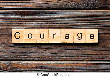 Courage word written on wood block. Courage text on wooden table for your desing, concept