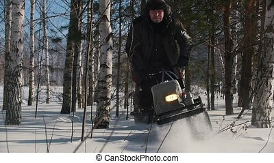 Courageous man maneuvering on mini snowmobile on deep snowdrifts in the winter forest between the trees