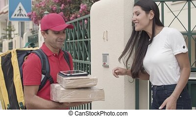Courier bringing packages to customers door, ringing doorbell. Woman confirming receiving parcel on tablet. Shipping or delivery service concept