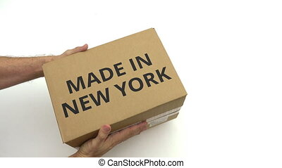 Courier delivers carton with MADE IN NEW YORK text on it -...