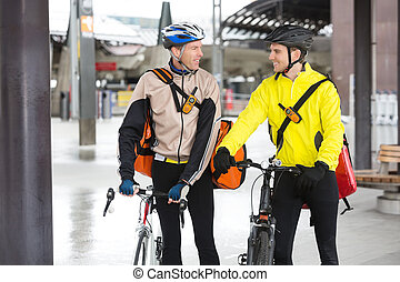 Courier Delivery Men With Bicycles Looking At Each Other -...