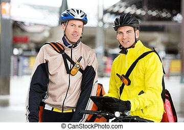 Courier Delivery Men With Bicycles Using Digital Tablet