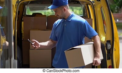 Courier hold box and taxt on phone. - Delivery Guy In Blue...