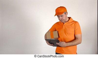 Courier in orange uniform delivering a parcel. Grey backround, isolated. 4K shot