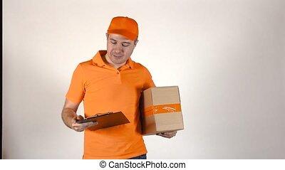 Courier in orange uniform delivering a parcel. Light grey backround, 4K studio shot