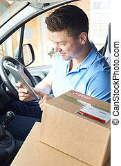 Courier In Van With Digital Tablet Delivering Package To Domestic House