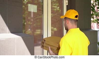 Courier in yellow uniform delivers pizza boxes to woman at doorway.