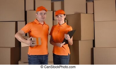 Couriers in orange uniform standing against brown cartboard boxes backround. Delivery company personel, 4K clip