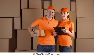 Couriers in orange uniform standing against brown carton stacks backround. Delivery company staff. 4K studio video