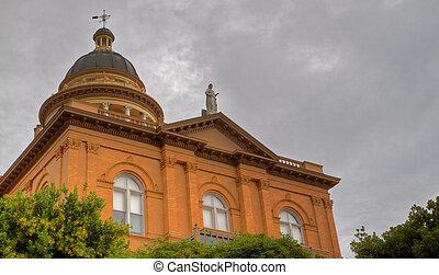 Courthouse oblique - Front facade of pillared tan brick...