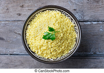 Couscous in bowl. Wooden background. Close up. Top view.