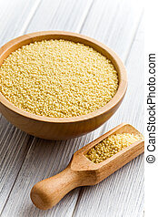 couscous in wooden bowl on kitchen table