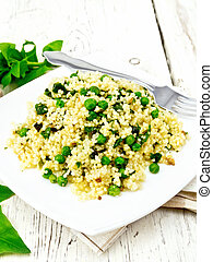 Couscous with spinach in plate on board