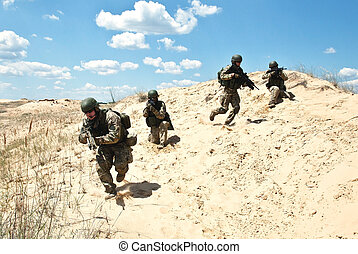 Cover me! - Squad of soldiers run through the desert through...