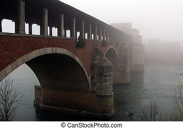 Covered bridge surrounded by fog in winter