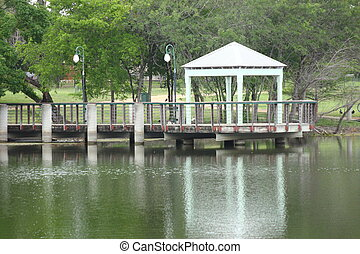 Covered fishing pier located on a lake or pond.