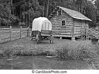 Covered Wagon Near Log Cabin Black and White
