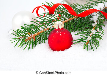 covered with snow branch of a Christmas tree and red ball on...